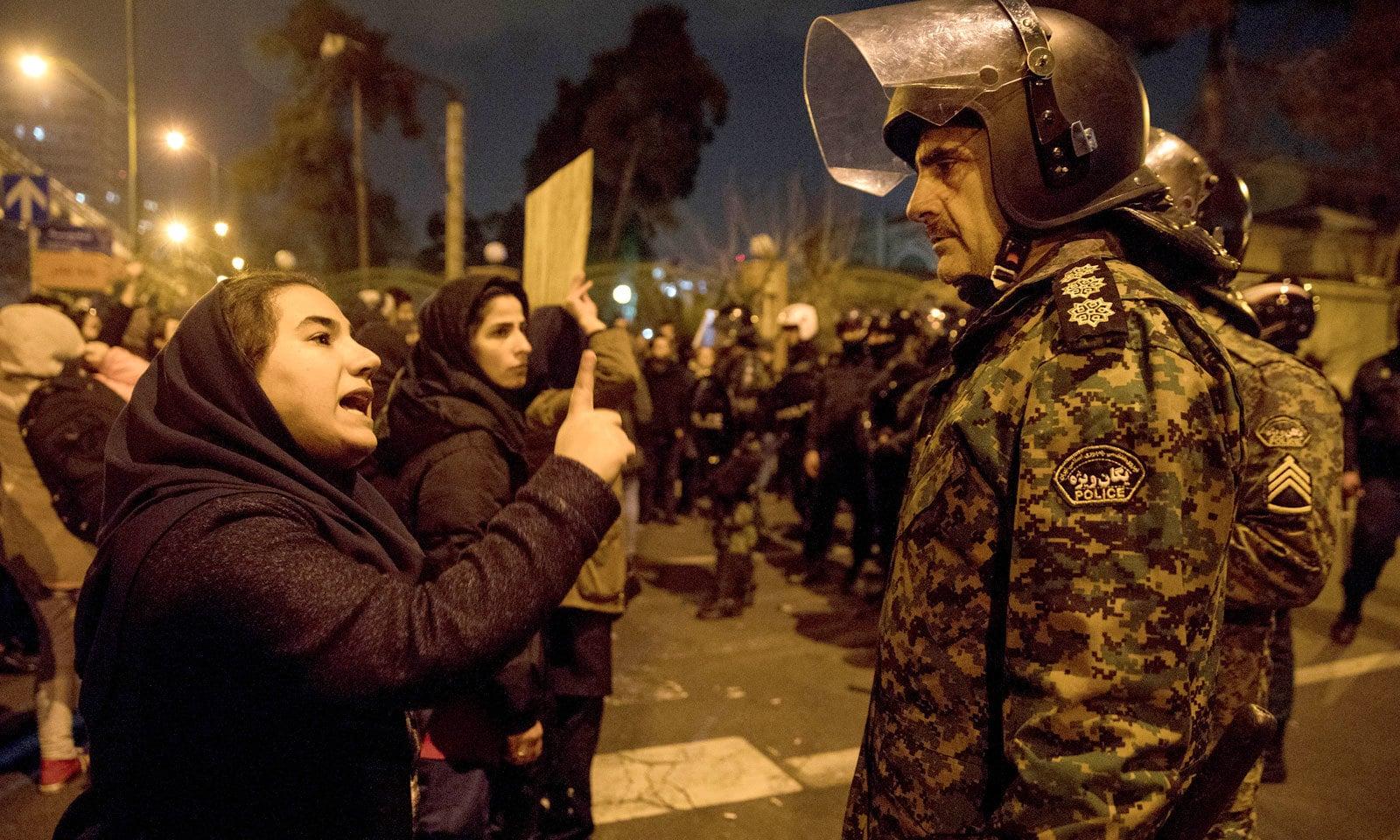 مظاہرے میں شریک ایک خاتون کا ایرانی سیکیورٹی اہلکاروں سے تکرار کا ایک منظر— فوٹو: اے پی