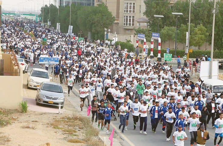Participants in the marathon pack a street in the Defence Housing Authority on Sunday.—PPI