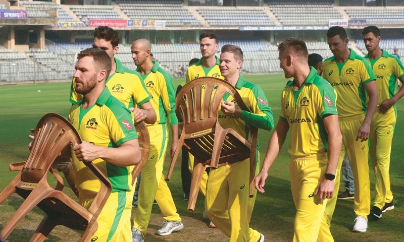 MUMBAI: Australian captain Aaron Finch (L) and Steve Smith carry chairs as the team walks back after a group photo session on Sunday.—AP