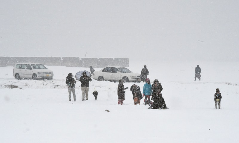 QUETTA: Families enjoying snowfall on a road here on Sunday.—AFP