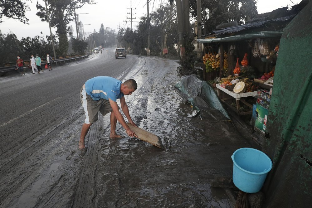 Residents cleans ash fall from Taal Volcano's eruption on Monday in Tagaytay, Cavite province, south of Manila, Philippines. ─ AP