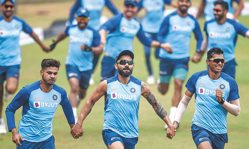 MUMBAI: Indian cricketers run holding hands as they attend a training session at the Wankhede Stadium on Monday.—AFP