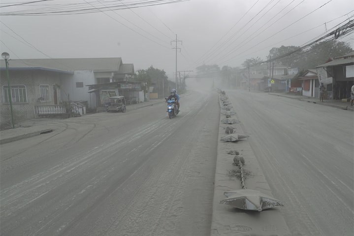 BATANGAS (Philippines): A man negotiates a road covered with ash spewed by Taal volcano.—AP