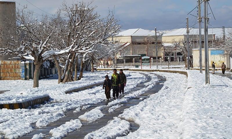 بلوچستان میں نوجوان برف پر چہل قدمی کرتے ہوئے—تصویر: اے ایف پی