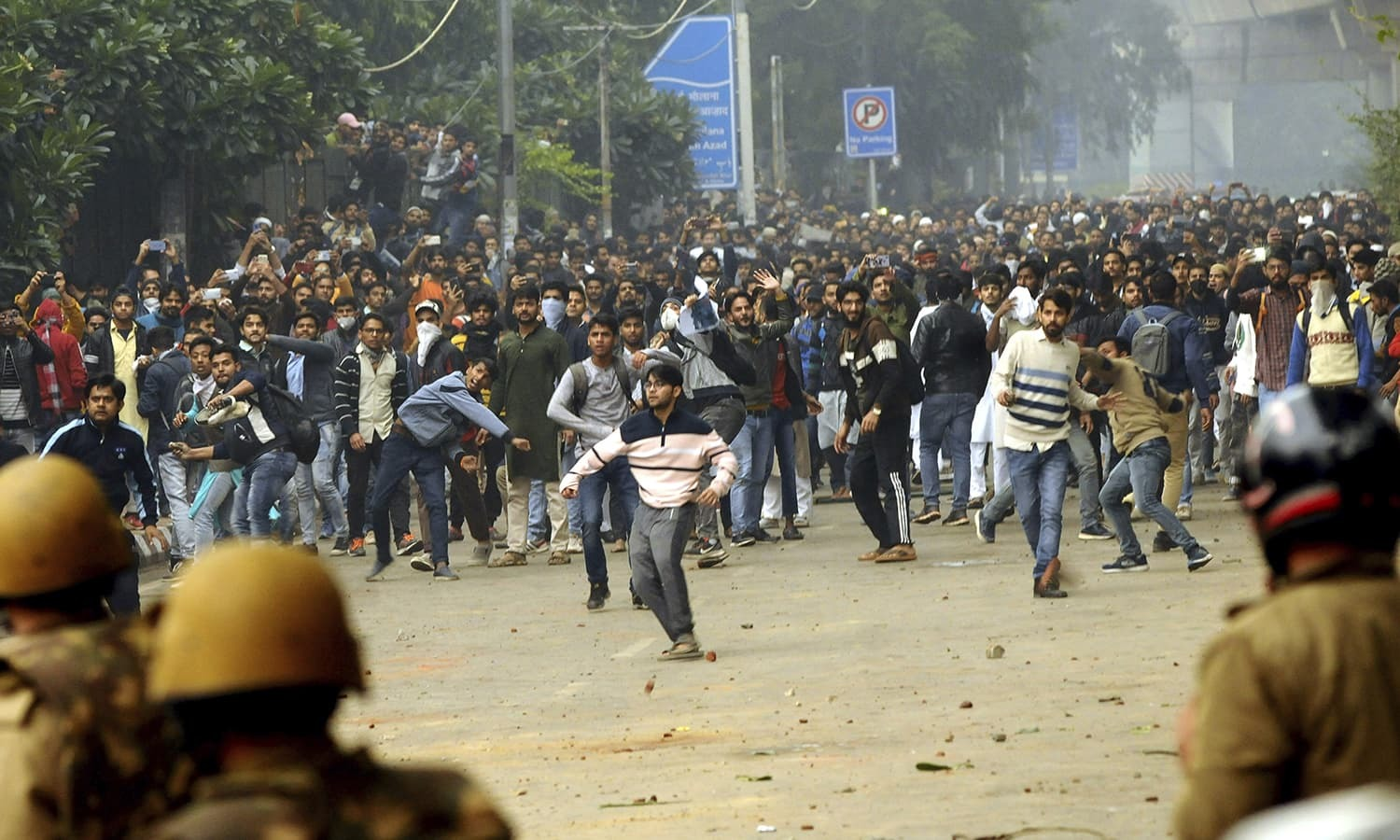 Students shout slogans and pelt stones outside the Jamia Millia Islamia University during a protest against the Citizenship Amendment Bill, in New Delhi, India, Friday, Dec. 13, 2019. Japanese Prime Minister Shinzo Abe is postponing a meeting with Prime Minister Narendra Modi in India's northeast. The region has been the site of continuing protests against a new law that grants citizenship to non-Muslims who migrated from neighboring countries. (AP Photo) — Copyright 2019 The Associated Press. All rights reserved.