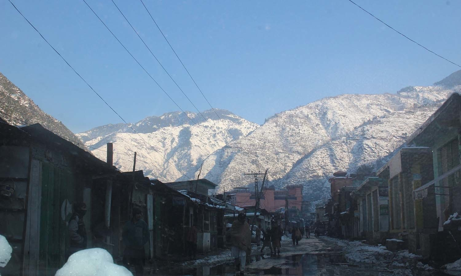 Snow-covered mountains look over the streets of Shangla. — Umar Bacha