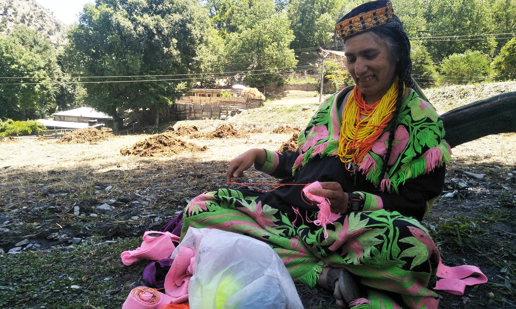 کیلاش قبیلے کی ایک خاتون کشیدہ کاری میں مصروف ہے—عظمت اکبر