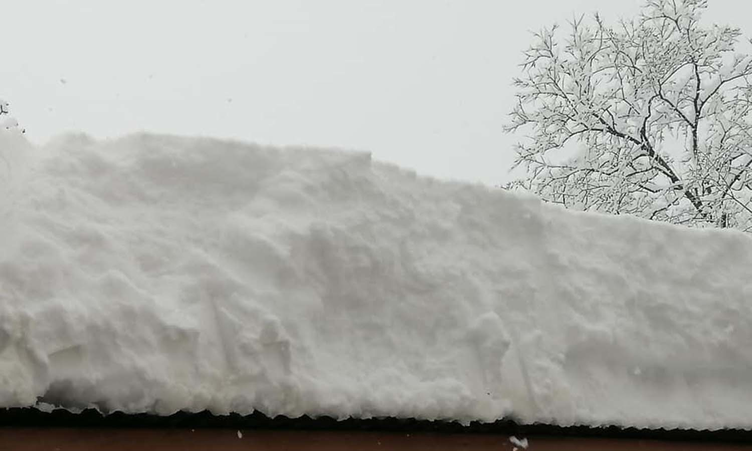 A thick layer of snow covers a rooftop in Shangla. — Umar Bacha