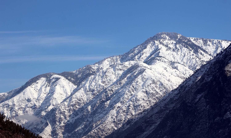 شانگلہ میں برف کی سفید چادر نے پہاڑوں کو ڈھکا ہوا ہے— فوٹو: عمر باچا