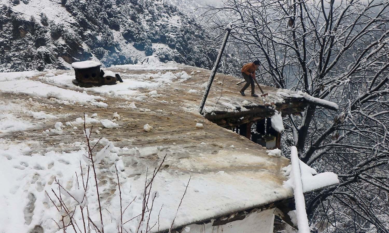 لائن آف کنٹرول کے قریب واقع وادی نیلم میں شدید برفباری کے بعد ایک بچہ اپنے گھر کی چھت سے برف ہٹا رہا ہے— فوٹو: رائٹرز