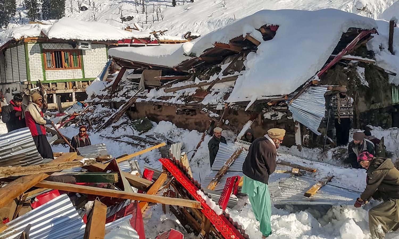 وادی نیلم میں برفانی تودہ گرنے سے تباہ ہونے والے مکان کے ڈھیر کو مقامی افراد ہٹانے میں مصروف ہیں— فوٹو: اے ایف پی
