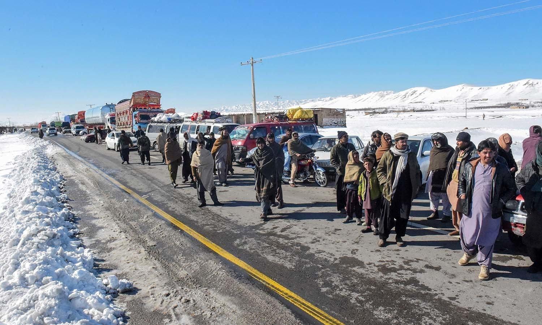 کوئٹہ سے 75 کلومیٹر دور واقع خانوزئی کے علاقے میں شدید برفباری کے سبب راستے بند ہو جانے کے بعد لوگ پیدل سفر کرنے پر مجبور ہوگئے— فوٹو: اے ایف پی