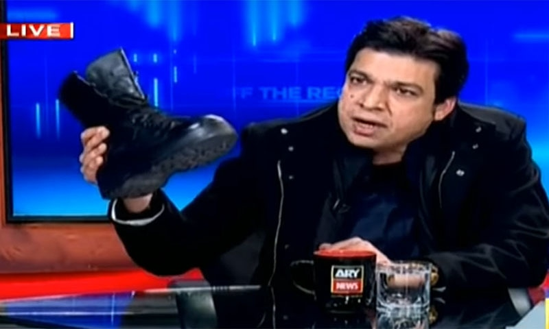 Faisal Vawda, a federal minister belonging to the Pakistan Tehreek-i-Insaf (PTI) brought an army boot to a live TV programme on Tuesday evening to heap scorn on the opposition Pakistan Peoples Party and Pakistan Muslim League-Nawaz for voting in favour of the recently-passed Army Act in parliament. — Screengrab via ARY News YouTube video