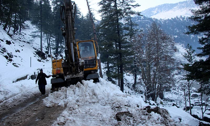 A man guides an excavator operator as they clear a snow-covered road in Neelum on Jan 14. — Reuters