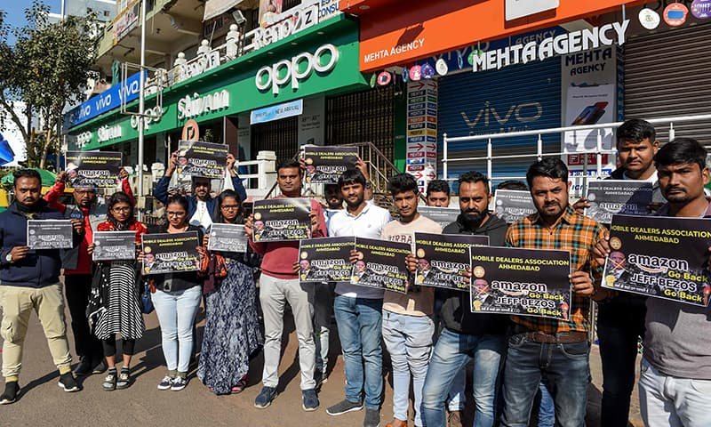 Mobile dealers and members of Ahmedabad Mobile Dealers Association hold placards as they protest against Amazon outside their closed mobile shops in Ahmedabad on January 15. — AFP