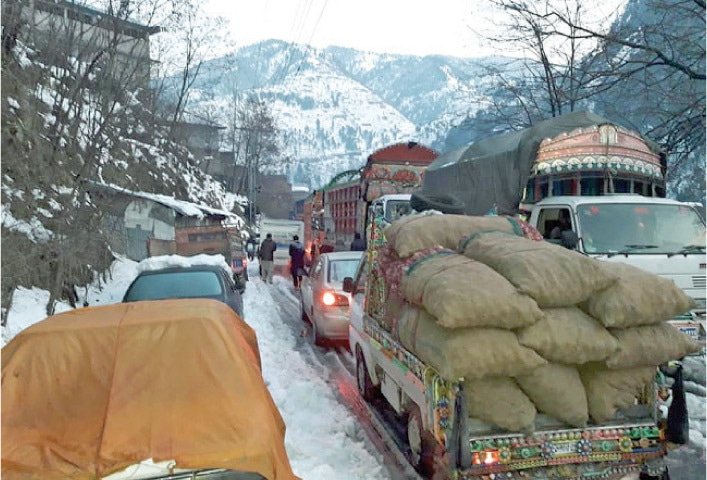 Traffic comes to a halt in Alpuri Bazaar, Shangla, on Wednesday due to heavy snowfall. — Dawn