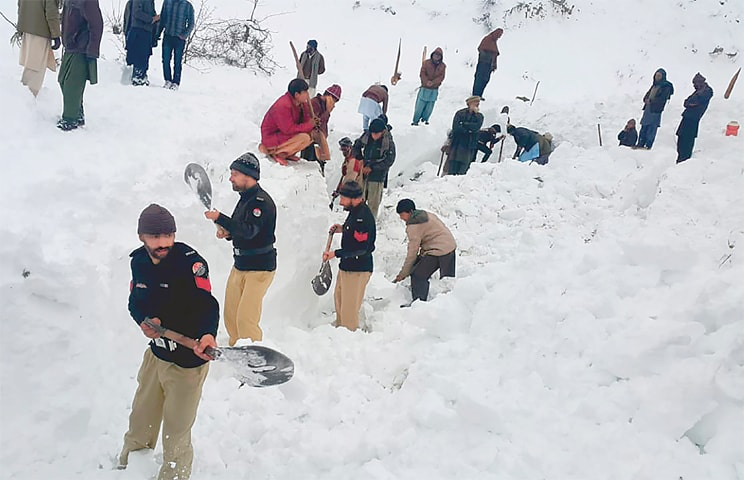 Police officers and residents dig to search bodies of victims of an avalanche in Doodnail village in Neelum Valley on Wednesday.—AP