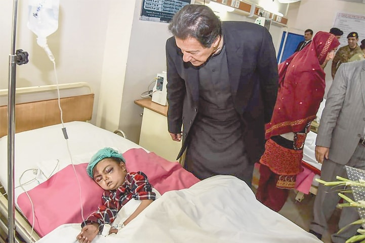 MUZAFFARABAD: Prime Minister Imran Khan looks at an injured girl during his visit to a hospital on Wednesday—AFP
