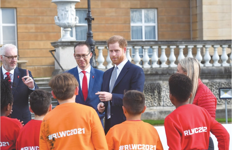 Prince Harry chats to schoolchildren before the draw for the Rugby League World Cup at Buckingham Palace on Thursday.—AFP