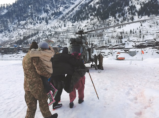 A SOLDIER escorts members of a stranded family to a helicopter in Neelum Valley. Search teams continued to pull out bodies on Thursday from homes destroyed by avalanches in Azad Kashmir.—AP