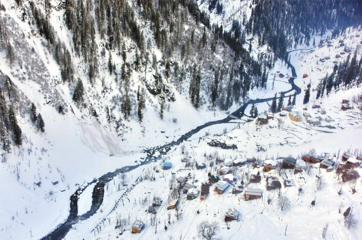 Houses covered with heavy snow pictured in Neelum Valley of Azad Jammu and Kashmir on Thursday.—AFP