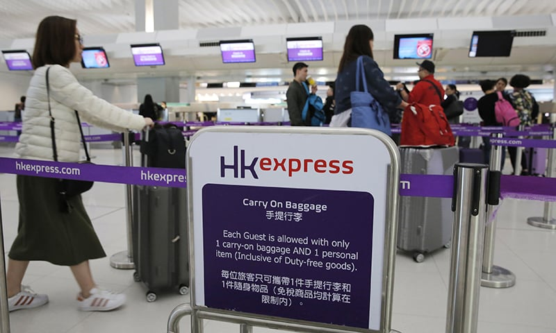 In this March 26, 2019 photo, passengers wait at the check-in counter of Hong Kong Express Airways at the Hong Kong International Airport. — AP