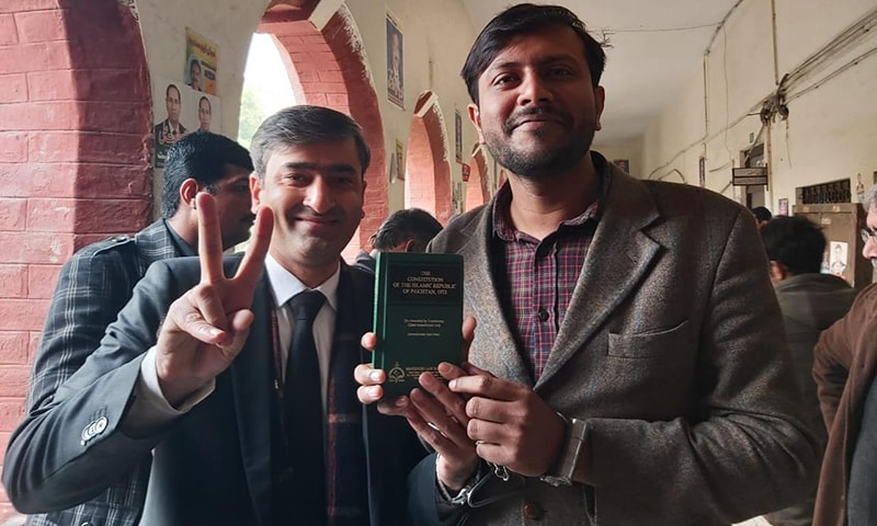 Journalist Azharul Haq Wahid (R) poses for a photo along with his lawyer while holding a copy of the Constitution of Pakistan during his court appearance on Friday. — Photo by author