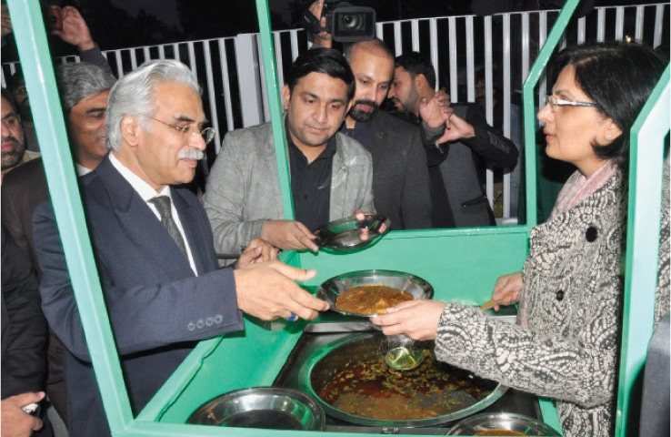 Dr Sania Nishtar gives food to Special Assistant to the Prime Minister on Health Dr Zafar Mirza at the Langar inaugurated at Pims on Friday. — White Star