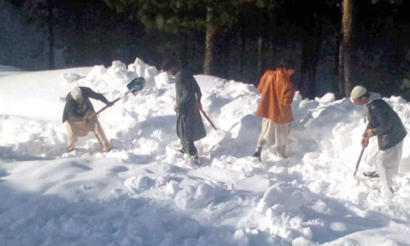 Locals clear a road on self-help basis in Mian Kallay Pagorai area of Shangla on Friday. — Dawn