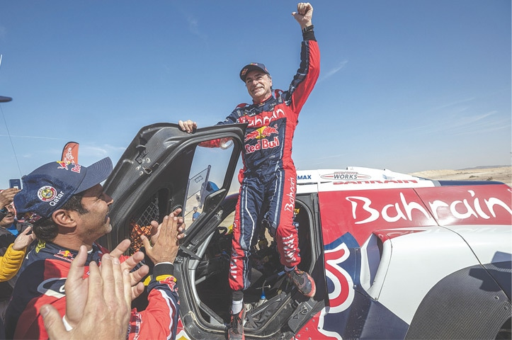 QIDDIYA: Carlos Sainz of Spain celebrates at the end of the 12th stage of the Dakar Rally on Friday.—AP