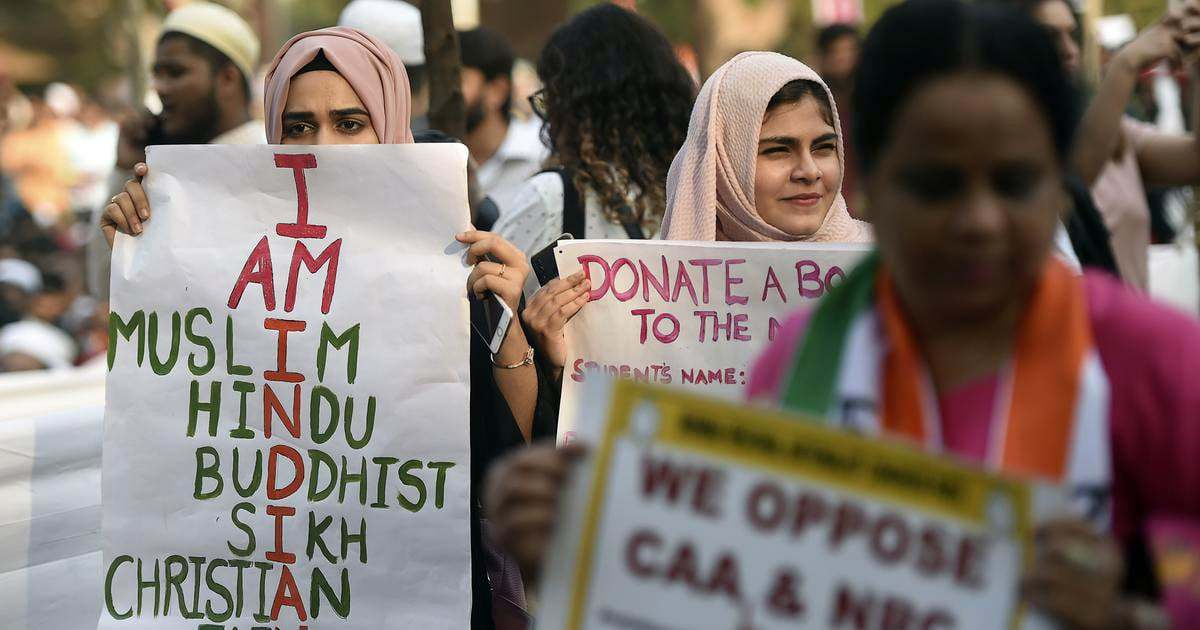 Protesters hold placards at a demonstration against the CAA in Mumbai, Dec 19, 2019. — AFP/File