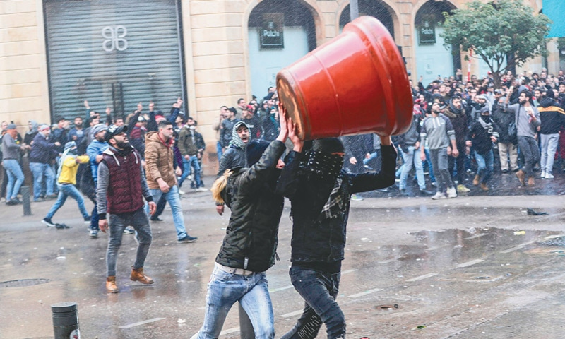Anti-government protesters attempt to throw a large plant pot at security forces taking cover during clashes in the central downtown district of the Lebanese capital on Saturday.—AFP