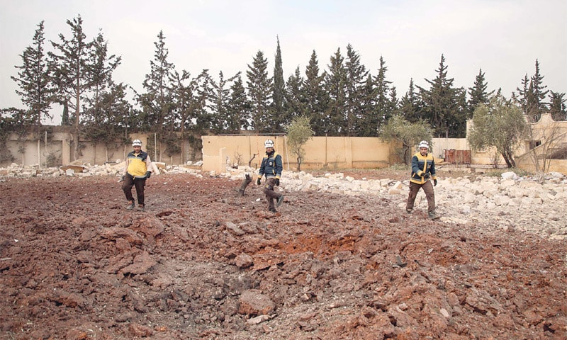 Members of the Syrian Civil Defence, also known as the White Helmets, stand around a crater left by an airstrike on a building in the town of Baleh, in the western countryside of the northern province of Aleppo on Saturday.—AFP