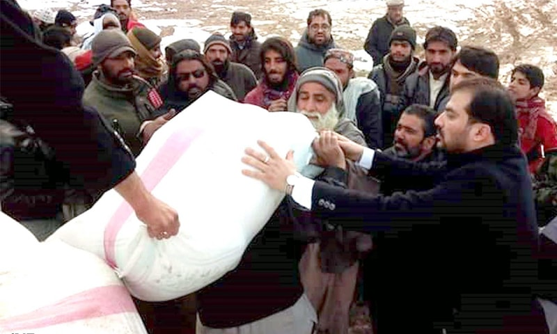 QUETTA: MPA Mubeen Khan Khilji distributes relief goods among snowfall-hit people  on Saturday.—INP