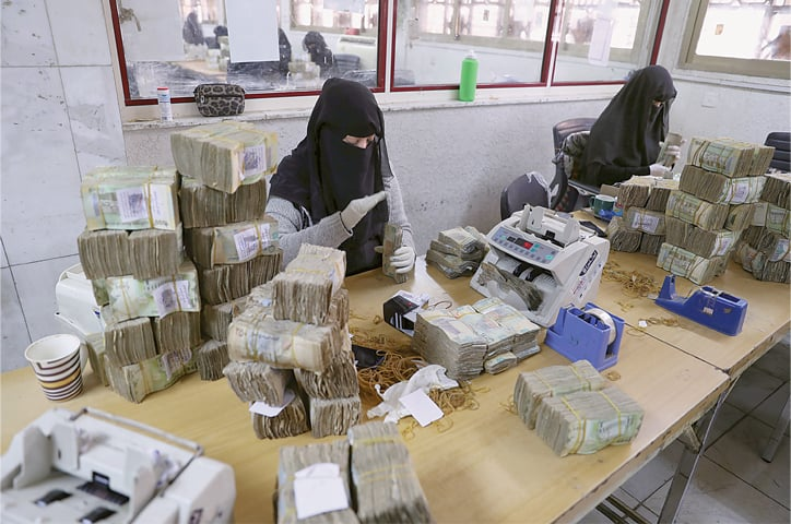 SANAA: In this Jan 7 photo, employees count bundles of Yemeni riyal at the Central Bank of Yemen.—Reuters