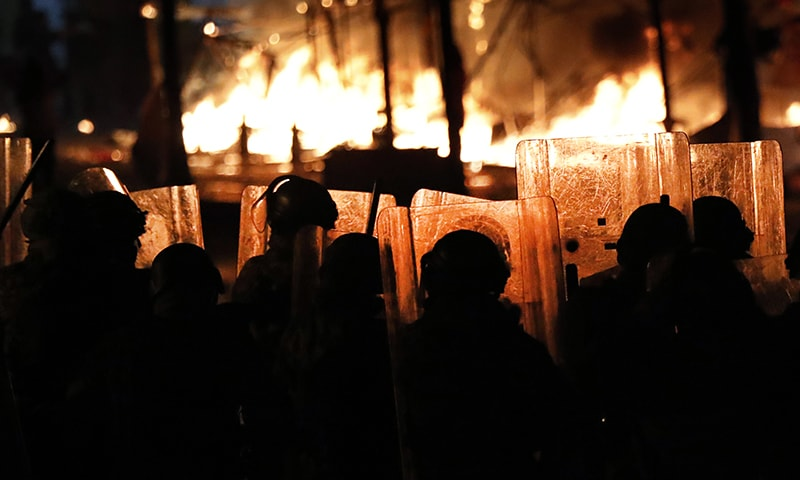 Riot policemen watch flames rise from the tents of anti-government protesters, which where set on fire by civilian men believed to be the private unit of the parliament guards, during ongoing protests against the political elites who have ruled the country for decades in Beirut on Jan 18. — AP