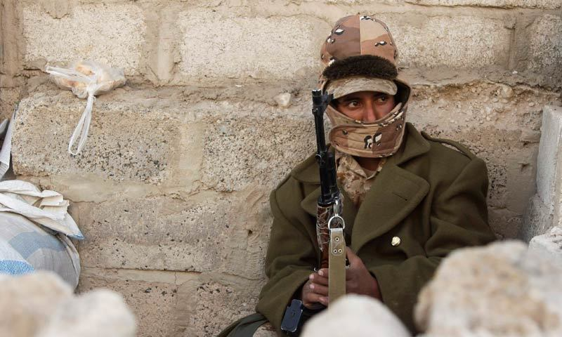 An army soldier sits near a checkpoint on a street in Sanaa, Feb 3, 2014. — Reuters