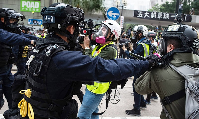 Police push a group of journalists after dispersing a crowd gathered for the 'universal siege on communists' rally at Chater Garden in Hong Kong on Sunday. — AFP
