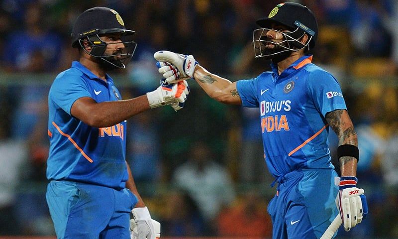 India's Virat Kohli (R) and Rohit Sharma greet each other during the third and last one day international (ODI) cricket match of a three-match series between India and Australia at the M. Chinnaswamy Stadium in Bangalore on Sunday. — AFP