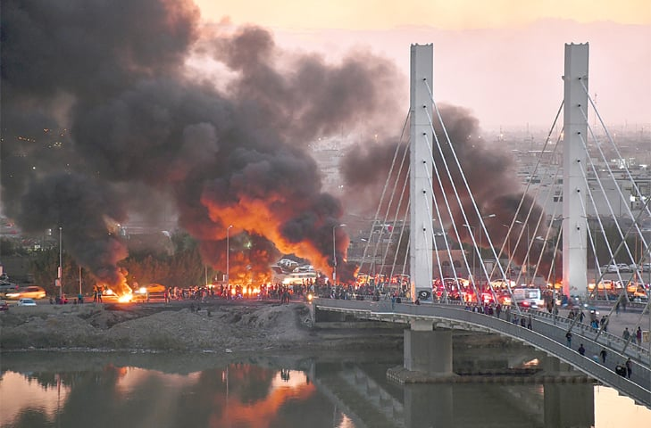ANTI-GOVERNMENT protesters block a bridge with debris and burning tyres in the Iraqi city of Nasiriyah.—AFP