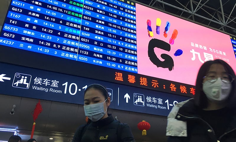 Passengers wearing masks walk under a train information board at the Beijing West Railway Station on Jan 20. — Reuters