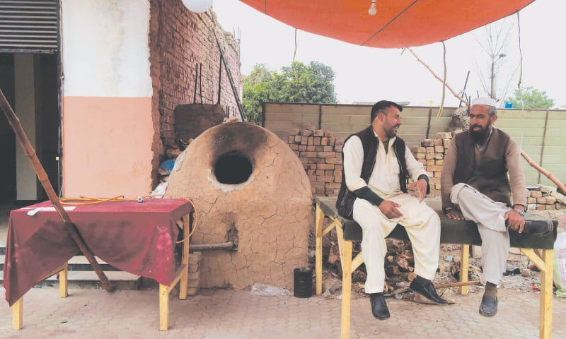 PESHAWAR: Two men sit in front of a closed bakery during a strike on Monday.—AFP