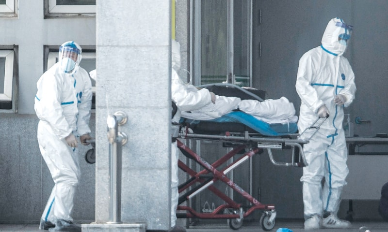 Wuhan (Hubei province, China): A patient is being carried into a hospital where those infected by a mysterious SARS-like virus are being treated.—AFP