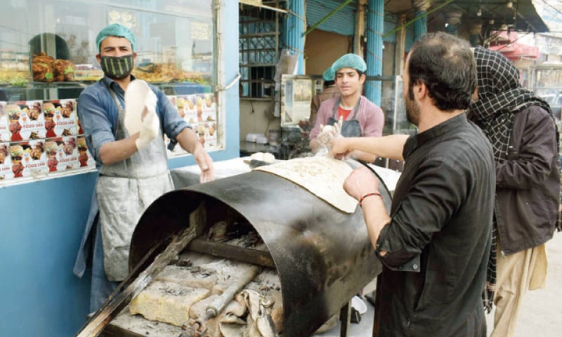 Workers make chapatis at an outlet as nanbais went on strike in Peshawar on Monday. — Photo by Abdul Majeed Goraya