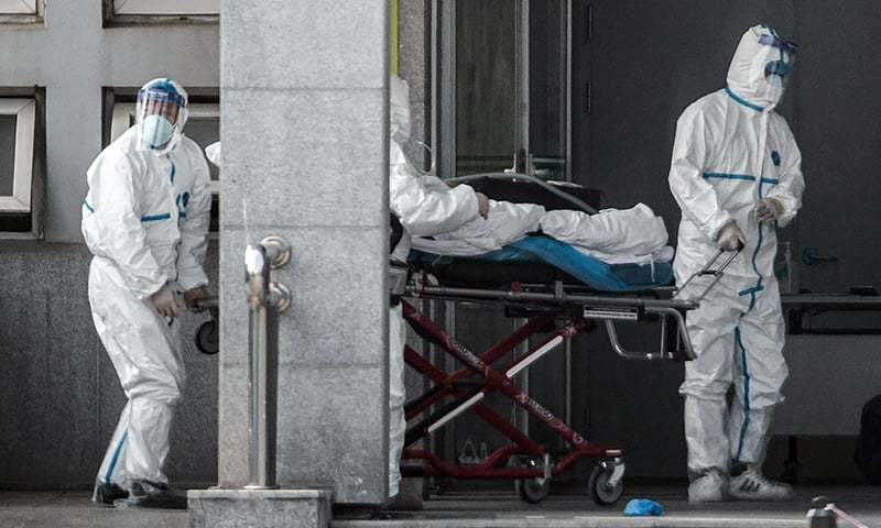 Medical staff members carry a patient into the Jinyintan hospital, where patients infected by a mysterious SARS-like virus are being treated, in Wuhan in China's central Hubei province on January 18. — AFP