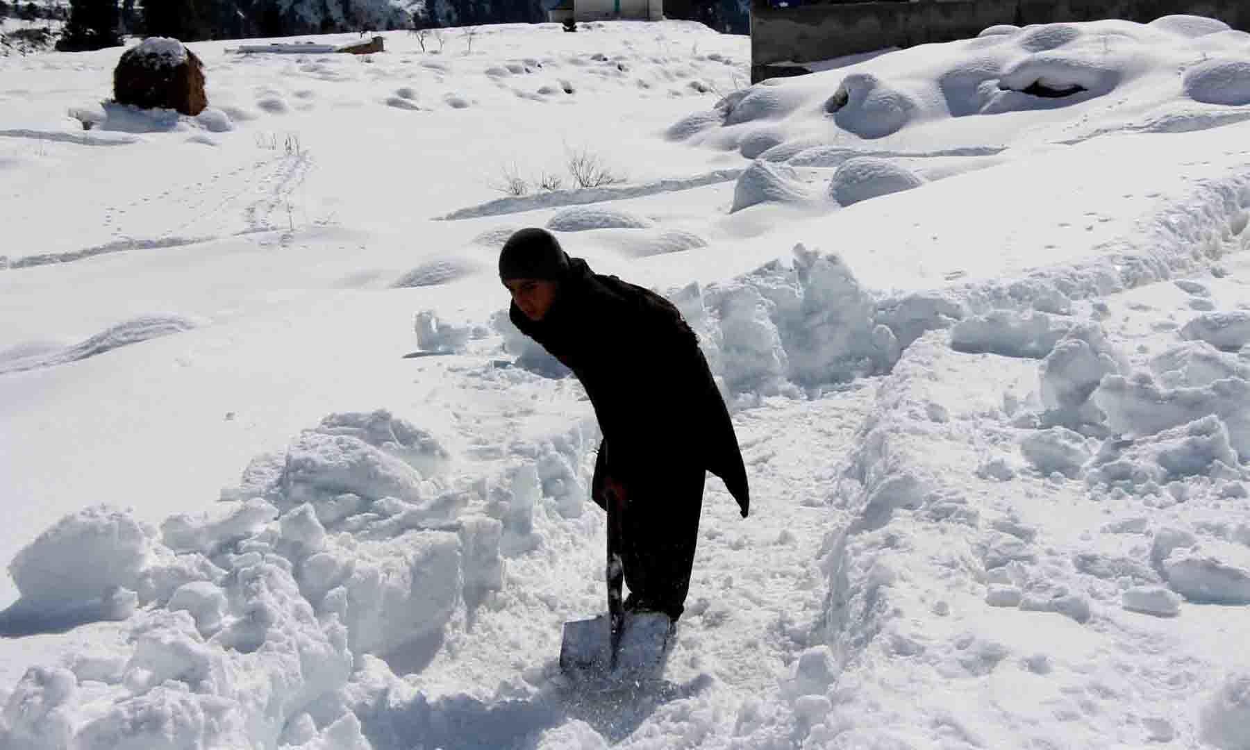 ایک مقامی بچہ گاؤں والوں کے لیے برف میں راستہ بنا رہا ہے