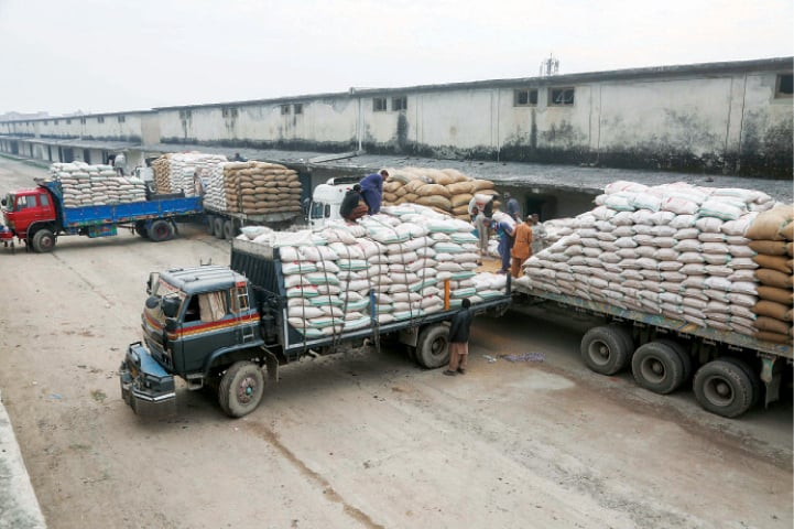 Trucks being loaded with sacks of wheat at the food department's Mughalpura godown for supply to the mills. — White Star
