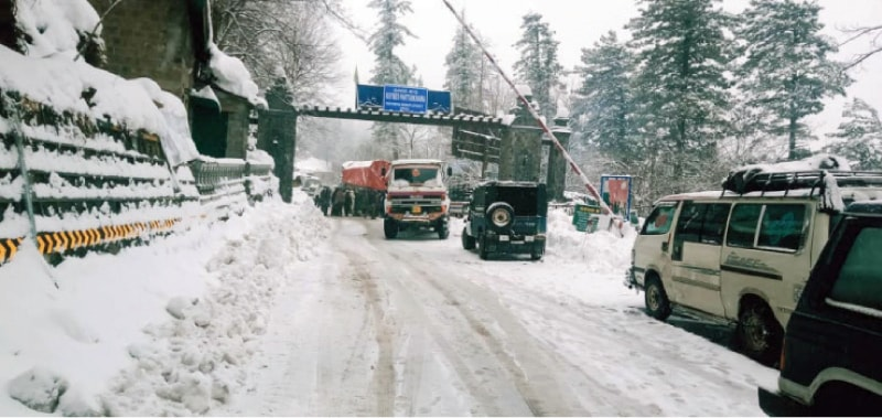 Traffic moves through snow in Barriyan Bazaar, a market on the border between Punjab and KP. — Photos by the writer