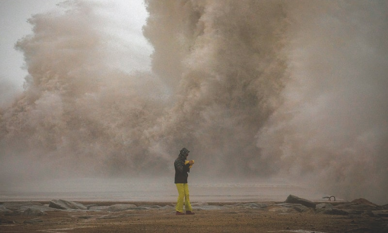 Barcelona: A woman photographs the Mediterranean Sea as waves hit the breakwater during the storm.—AP