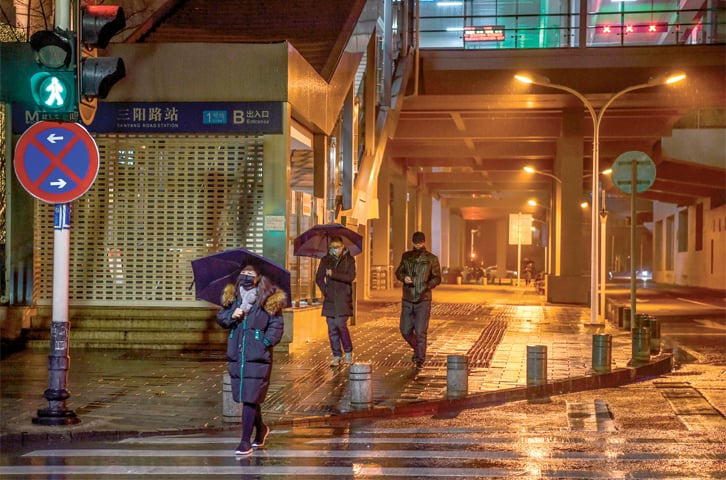 WUHAN (China): A few people wearing masks walk in a largely deserted street on Thursday.—AFP
